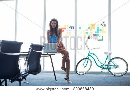 Portrait of female executive working over laptop in office