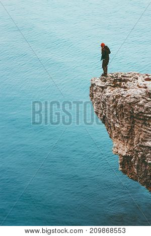 Traveler standing on cliff edge above sea alone Travel Lifestyle concept adventure active vacations outdoor solitude emotions