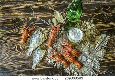 Beer with foam in a glass and a bottle of beer with a snack of boiled crawfish and dried salted fish on dark wood boards