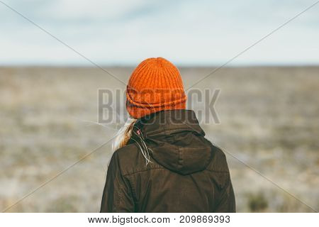 Woman walking alone prairie on background Travel Lifestyle concept outdoor Solitude melancholy emotions