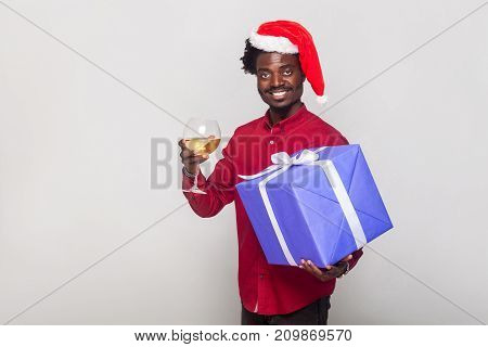Happiness Afro Man In Red Cap Holding Champagne Glass And Gift Box, Looking At Camera And Toothy Smi