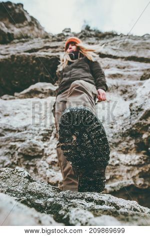 Woman traveler climbing at rocky mountains Travel Lifestyle wanderlust adventure concept summer vacations view under feet boots perspective