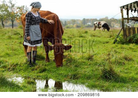 the girl the farmer in the field with the cows after a rain