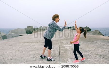 Senior sportswoman and little girl high five by sea pier