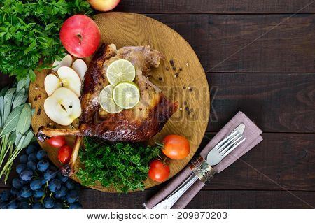 Baked goose legs served with apples vegetables grapes greens on a round oak tray on a dark wooden table. Top view.