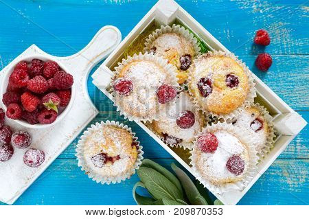 Curd cakes (muffins) with raspberries decorated with powdered sugar. Serve in a white wooden box. Fresh raspberries in a ceramic bowl. Top view.