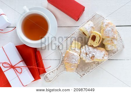 Homemade croissants with fruit jam decorated with powdered sugar with a cup of morning tea on a white wooden background scattered gift white and red boxes tied with a twine. Top view.