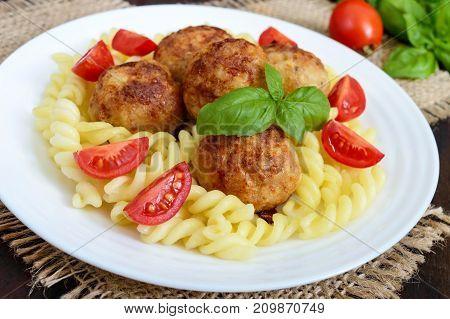 Pasta futsilli with meat balls cherry tomatoes basil on a white plate on a dark wooden background.