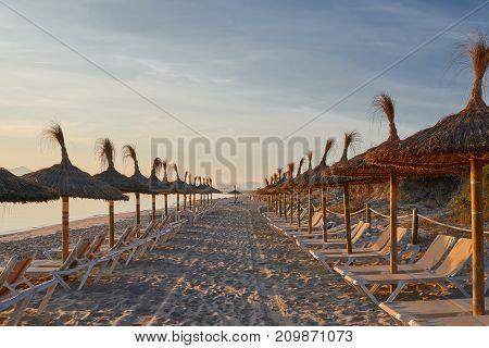 Sunrise On A Resort Beach With Umbrellas