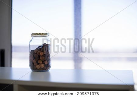 Close-up of coins in jar in office