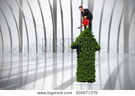 Businessman watering with red can against white room with large window overlooking city