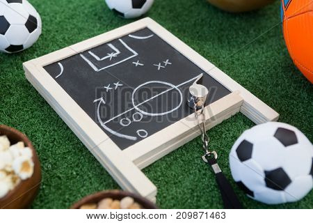 Close-up of strategy board, whistle and football on artificial grass