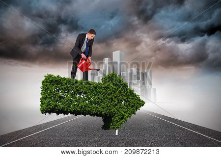 Businessman holding red watering can against cityscape on stormy landscape background