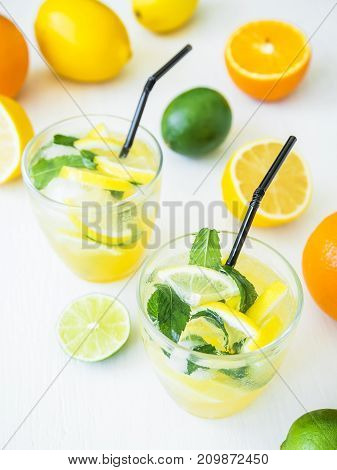 Fresh citrus lemonade made of limes and lemons in glasses. Tasty drinks with ice