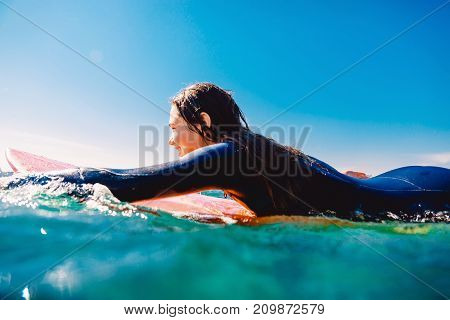 Surf girl on the surfboard. Woman with surfboard in ocean during surfing. Surfer and ocean