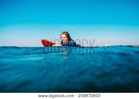 Surf girl on surfboard in ocean. Woman is during surfing. Surfer and ocean