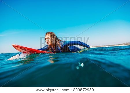 Surfer girl on surfboard. Woman in ocean during surfing.