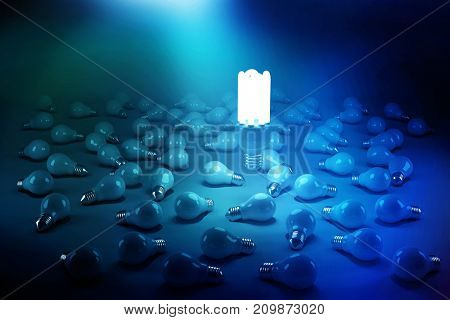 Digitally generated image of lit energy efficient lightbulb over bulbs on black background