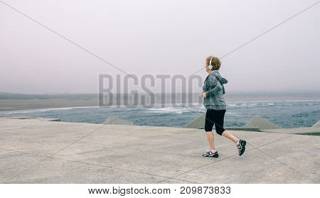 Back view of senior sportswoman with headphones running by sea pier
