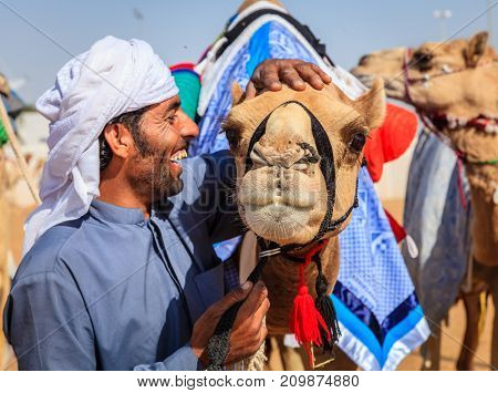 Dubai, United Arab Emirates - March 25, 2016: Camel handler with his animal at Dubai Camel Racing Club