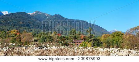 Pirin snow peaks mountains panorama and colorful autumn trees, Bansko, Bulgaria