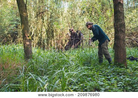 Man In Forest Scattering Lure For Roe Deer.