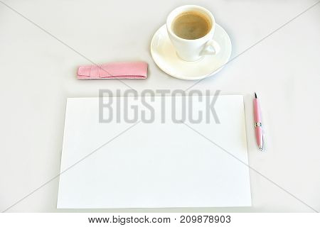 Espresso coffee, sheet of paper, pink pen and pen case on a desk