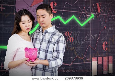 Couple holding their piggy bank  against red arrow
