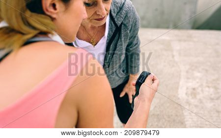 Senior woman looking smart watch with female coach outdoors
