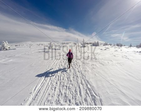 Running woman on winter trail snow and white mountains. Young happy girl with backpack cross country running in mountains. Female trail runner jogging exercising outdoors.