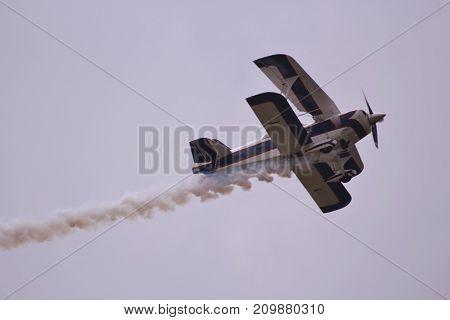 smoking aerobatic airplane fly pass in the sky