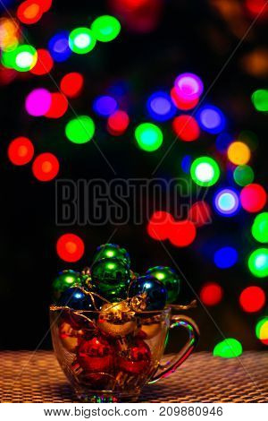Glass cup full of Christmas decorations on the background of Christmas tree garland in blur