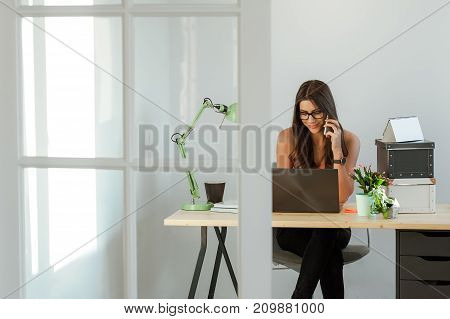 Entrepreneur pretty woman sitting at home desk working on laptop computer and talking on mobile phone, smiling.