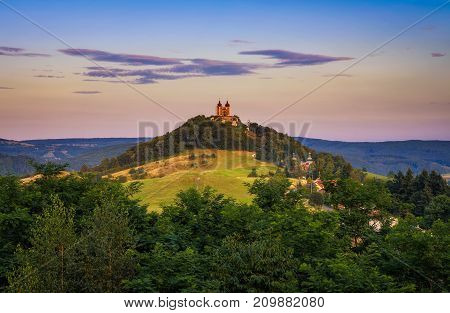 Upper church with two towers and baroque calvary in Banska Stiavnica, Slovaka at sunset. Banska Stiavnica is a completely preserved medieval town and a popular tourist destination.