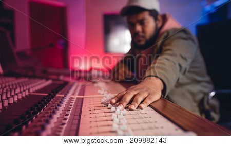 Young man hands working on music mixer. Sound engineer mixing audio in recording studio.
