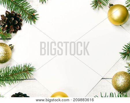 White wooden Christmas background. Border decorated fir branches and pin cones, golden ornamet. Copy space for holiday greetings. lovely xmas festive card. Top view. Flat