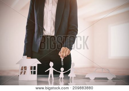 woman drawing a car, a family and a house against white big room with windows