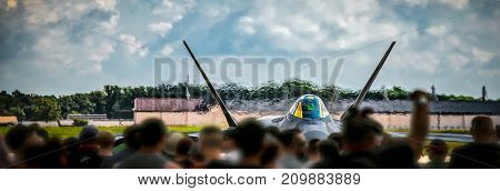 A crowd watches a jet warming up and preparing for take off.