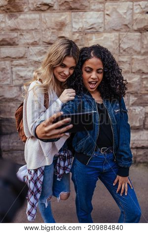 Cheerful girls taking a selfie using mobile phone. Women standing outdoors and making faces while posing for a selfie.