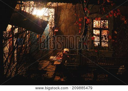 Old House With Saturnine Red Walls, A Porch Lit By Bulb Light And Courtyard At Autumn Evening. Conce