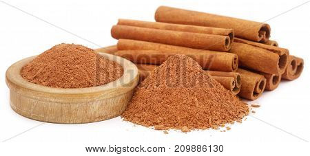 Bunch of some fresh aromatic cinnamon with powder spice over white background