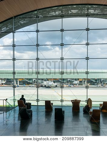 Paris, France, April 1 2017: Looking out a large ellipsoid window at Charles De Gaulle airport