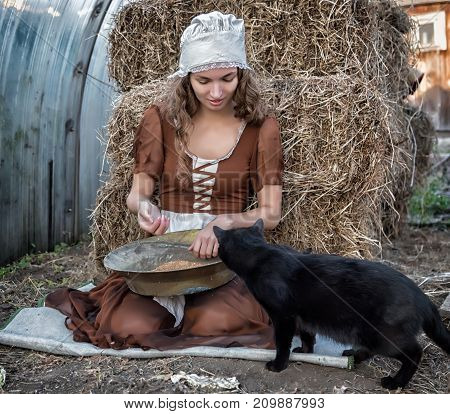 beautiful woman in a rustic dress sits on a hay and sifts the grain. Cinderella style poster