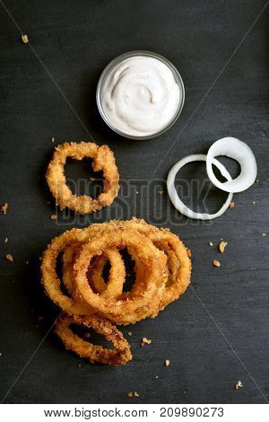 Fried onion rings with sauce on black stone background top view