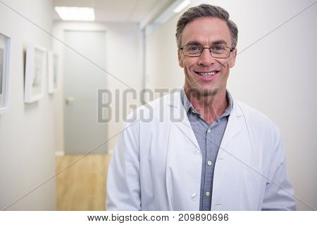 Portrait of smiling dentist standing at lobby in dental clinic