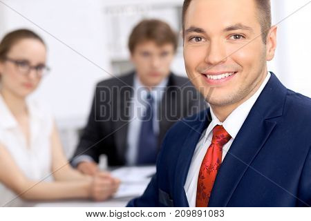 Portrait of cheerful smiling business man  against a group of business people at a meeting.