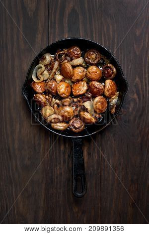 Fried mushrooms in frying pan on wooden background top view