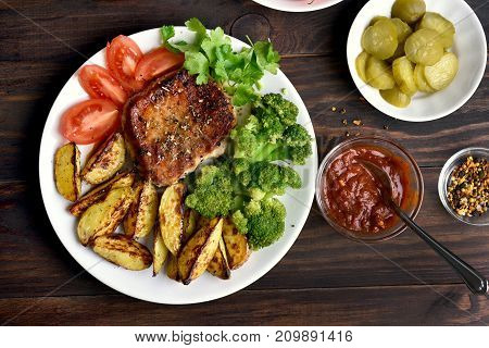 Roasted meat with broccoli potato wedges and tomato slices on wooden background top view