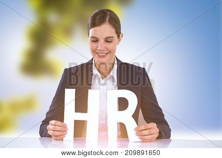 woman looking letters H and R against trees against clear blue sky on sunny day