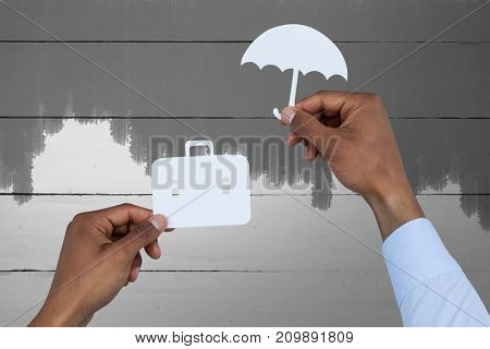 hands holding a schoolbag and an umbrella in paper against green paint on fence